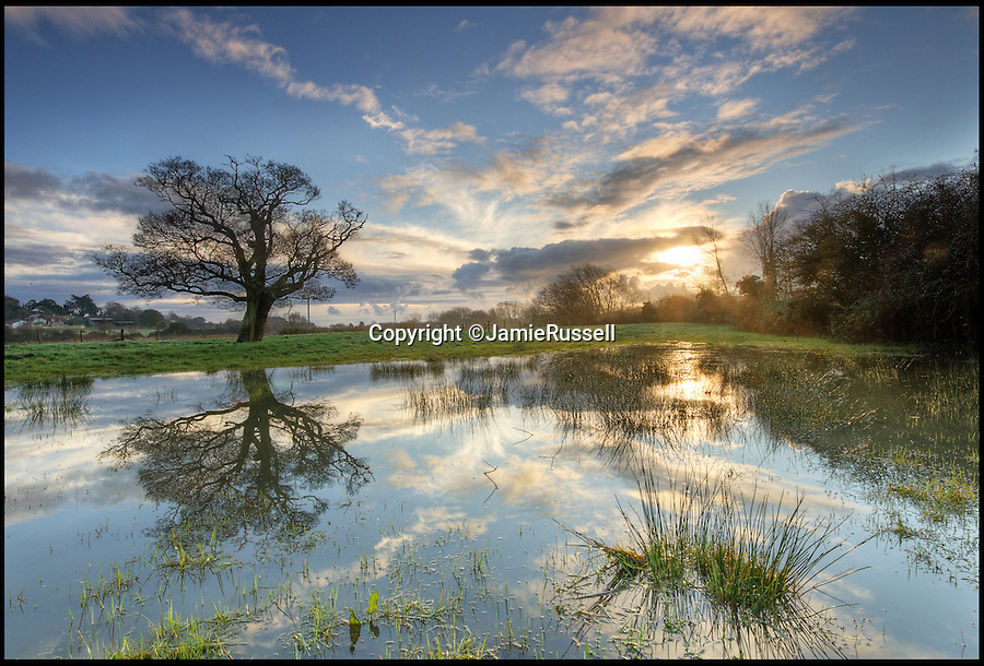 BNPS.co.uk (01202 558833)<br /> Pic: JamieRussell/BNPS<br /> <br /> ***Please Use Full Byline***<br /> <br /> The sun rises over the boggy flood plain at Alverstone.<br /> <br /> Stunning photographs have revealed a turbulent side to the normally genteel Isle of Wight.<br /> <br /> The seemingly benign south coast holiday destination has been catalogued over a stormy year by local photographer Jamie Russell, and his astonishing pictures reveal the dramatic changes in weather that roll across the UK in just 12 months.<br /> <br /> Lightning storms, ice, floods, gales and blizzards have all been captured by the intrepid photographer who frequently got up in the middle of the night to capture the climatic chaos.<br /> <br /> Looking at these pictures prospective holidaymakers could be forgiven for thinking twice about a gentle staycation on the south coast island.