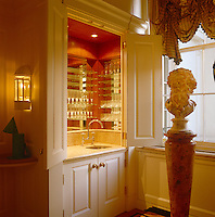 In the living room of a London town house a cocktail bar with integral lighting and a butler's sink has been concealed behind the doors of a cupboard