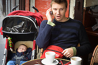 A father talking on his mobile phone in a cafe whilst his son sleeps in his pushchair.