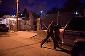 Nogales, Arizona.USA.October 24, 2006..A US border patrolman searches and detain one of four Mexicans that had jumped the fence from the Mexican side of Nogales to the US side before placing him in his vehicle.