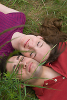 Couple laying in grassy field