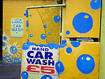 Yellow and blue-theme walls outside a local carwash business in south London.