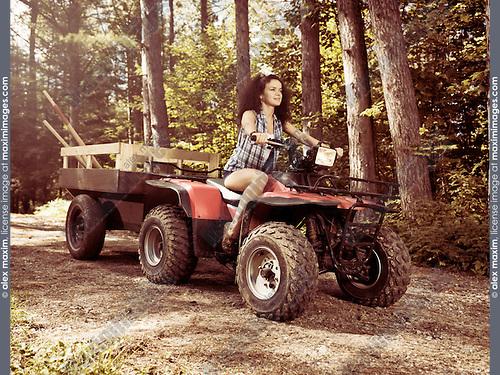 Young farm woman gardener riding an ATV with a trailer along tree lined country road. Muskoka, Ontario, Canada.