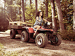 Young farm woman gardener riding an ATV with a trailer along tree lined country road. Muskoka, Ontario, Canada.