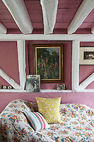 A floral quilt is thrown over the chaise longue in the living room, a quick and easy way of ringing the changes from season to season