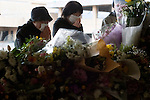 Mourners lay flowers and say prayers at a makeshift altar at the entrance to the municipal sports center in Rikuzentakata, Iwate Prefecture, Japan on 11 Mar 2012. .Photographer: Robert Gilhooly