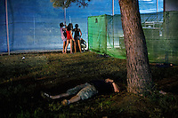 BENIC&Agrave;SSIM, SPAIN - An English tourist lies passed out in the grass while a group of girls take turns urniating in a corner of the festival site. ..Described by some as a Mediterranean Glastonbury, the Festival Internacional de Benic&agrave;ssim (FIB) is the largest music festival outside the UK to target British visitors. In 2010, seven of the eight main headline slots were filled by English bands...A small coastal town of 13,000 inhabitants, Benic&agrave;ssim hosted some 200,000 visitors in 2009, with 40% of those believed to be coming from the UK. In 2010, attendances fell to 127,000 visitors but the percentage of UK visitors is believed to have risen.