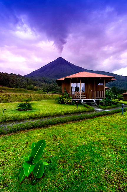 The Very Active Arenal Volcano Rises Behind A Cabin At The Lomas de Volcano Eco Lodge In La Fortuna, Costa Rica.