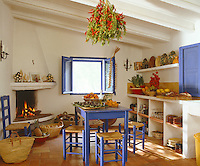 Traditional Mediterranean-blue paint brightens the furniture and window frame in this whitewashed kitchen