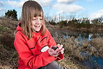 Young girl holding a common toad, Scotland