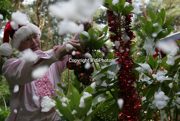 Foto: VidiPhoto..HENGELO (GLD) - Dreaming of a white Christmas, terwijl de mussen van het dak vallen van de warmte. Bij een temperatuur van 25 graden, hartje zomer, brengt Vincent Versteegen uit het Gelderse Hengelo donderdag alles in gereedheid voor een Kerstmarkt die zondag in Zelhem in de Achterhoek wordt gehouden. Een Kerstmarkt met een heuse Kerstman, kraampjes, glühwijn, levende kerststal, arreslee en een 'ijsbaan'. De opbrengst is voor een zorgboerderij in Angerlo die geen subsidie meer krijgt. De Achterhoeker heeft inmiddels de (inter)nationale pers weten te interesseren voor het 'warme' winterfenomeen.
