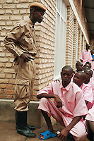 Rwanda. Southern province. District of Muhanga. Central jail of Gitarama. A group of black teenager boys, wearing the pink prisoner's clothes, kneel down. A prison warder, dressed with a beige sandy army uniform, stands up. Black plastic boots. Bricks wall. Minors block. Minors in detention. Detention pending trial and after trial, when sentenced to prison. The non-governmental organization (NGO) Fondation DiDé - Dignité en détention runs the Encademi (Encadrement des mineurs) program. Prison centrale de Gitarama. Quartier des mineurs.  © 2007 Didier Ruef