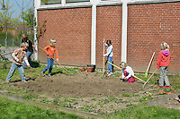 Schulgarten, Fläche am Schulgebäude, auf der ein Schmetterlingsgarten angelegt werden soll, Garten der Grundschule Nusse wird als Projektarbeit von einer 1. Klasse gestaltet, Kinder lockern den Boden mit Hacken und Harken, Gartenarbeit