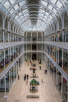 Central Hall at the National Museum of Scotland, Edinburgh.  .The National Museum results from a merger of the Museum of Scotland, built in 1998, and the former Royal Museum, built in 1861. After a massive renovation, the building re-opened in July 2011.  Going through the different halls, and passing from the new to the old from one hall to the next is a peculiar yet pleasant characteristic of the museum.  .Pictured is the great hall, part of the former Royal Museum, with its cast iron construction rising the full height of the building, and ending in a magnificent skylight.