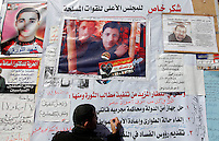 A man wrties on a wall with slogans and pictures of people that died during the revolution. Tahrir square after the revolution that saw president Hosni Mubarak ousted from office. Some protesters still occupied the Tahrir Square until March 9, when they were chased away by armed men,  while life in other parts of the city returned to normal.