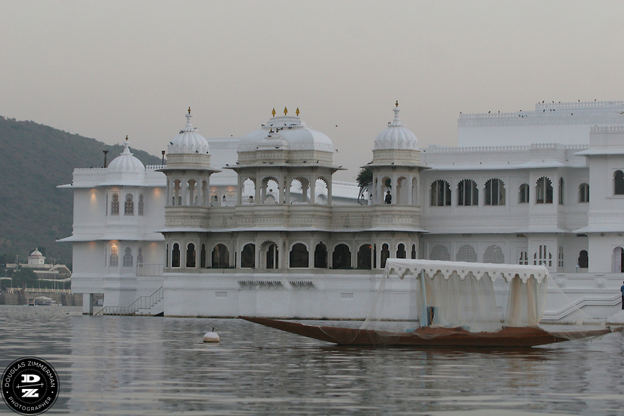 """View of the Lake Palace Hotel, which sits on Jagniwas Island in the center of Pichola Lake, in Udaipur, Rajasthan, India.  Udaipur is located in a valley surrounded by the Aravalli hills, and at its center is the Pichola Lake.  The scenic city has been described as """"the most romantic spot on the continent of India"""" (by Colonel James Tod).  Photograph by Douglas ZImmerman"""