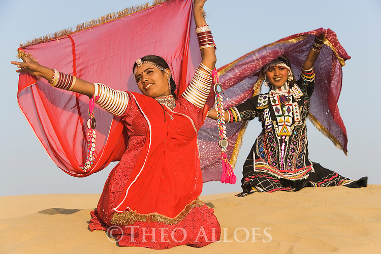 Rajasthani dancers in traditional costumes performing on sand dunes in the Thar Desert; Rajasthan, India ---Model Released