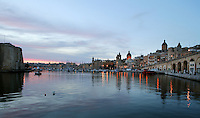 General view of the harbour of Valletta, Malta, pictured on June 5, 2008, in the evening. The Republic of Malta consists of seven islands in the Mediterranean Sea of which Malta, Gozo and Comino have been inhabited since c.5,200 BC. It has been ruled by Phoenicians (Malat is Punic for safe haven), Greeks, Romans, Fatimids, Sicilians, Knights of St John, French and the British, from whom it became independent in 1964. Nine of Malta's important historical monuments are UNESCO World Heritage Sites, including  the capital city, Valletta, also known as the Fortress City. Built in the late 16th century and mainly Baroque in style it is named after its founder Jean Parisot de Valette (c.1494-1568), Grand Master of the Order of St John. In this image the quiet waters of the harbour reflect the evening sky and the lights of the quayside. Picture by Manuel Cohen.