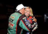 Sept. 1, 2012; Claremont, IN, USA: NHRA funny car driver Courtney Force (right) is kissed by father John Force after qualifying number one during qualifying for the US Nationals at Lucas Oil Raceway. Mandatory Credit: Mark J. Rebilas-