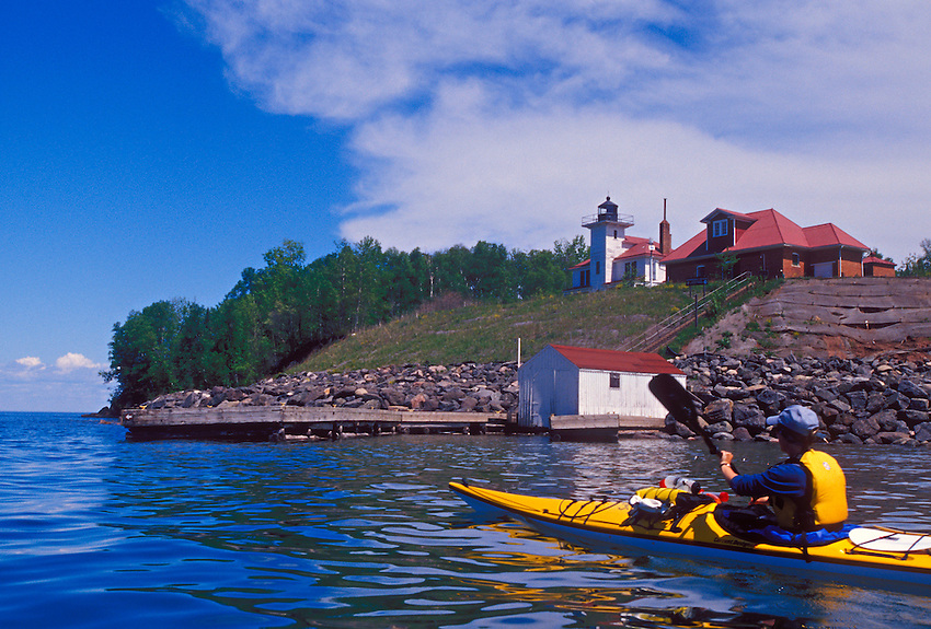 A sea kayaker paddles past the Raspberry Island Lighthouse in Apostle Islands National Lakeshore near Bayfield, Wis.