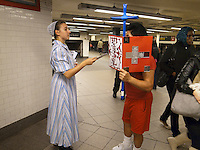 USA. New York City. Union Square. Subway station. Unexpected religious encounteer betweeen a Mennonites woman proselytizing, and a man calling himself &quot;The Angel&quot;, who carries a blue catholic cross in his hands. Mosaic tiles on wall. 22.10.2011 &copy; 2011 Didier Ruef