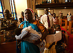 Mary Dieng Mai, holds her baby boy, Nyang, during services at the Capitol Hill Lutheran Church in Des Moines, Iowa, where their family worships every Sunday.  On this day, the baby would be baptized.  The family came to America 9 years ago because of religious persecution from Muslims in their native country of Sudan.  Beginning in the summer of 1992 Sudanese refugees began arriving in Des Moines through the efforts of the Lutheran Immigration and Refugee Services.  They now number over 800 in Iowa.  The Mai family arrived in 1998, seeking not only freedom of religion, but from a war that was tearing apart their country.   Just two years ago they moved into their new home in a better and safer neighborhood.  But  home for the Mai's is not just the four walls of a house, but America itself, where they have been able to build a new life.