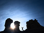 man with arms raised and sunshine surrounned by silhouetted sandstone rock formation pinnacles.  mesa de cuba, northern new mexico, usa.