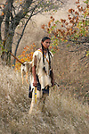 An Native American Indian walking through the grass during the fall who is tracking game