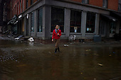 New York, New York.October 30, 2012..A Japanese reporter in high-top-boots stands in a puddle of water in lower Manhattan to record a segment about the effects of Hurricane Sandy.