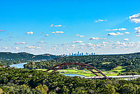 This is an image of the Auatin 360 Bridge or the Pennybacker Bridge where you can this section of the Colorado River called Lake Austin along with the skyline of the city in the distant view.  The downtown is a good distance from this location you can see the hills one of which is Mount Bonnel.