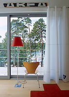 A chair is positioned infront of the huge picture window to take advantage of the spectacular view over the deck towards the pine trees and lake