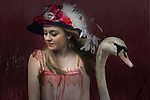 Young blond female teenager dressed in 1920's style, with a hat and feathers and a white swan