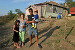 """THIS PHOTO IS AVAILABLE AS A PRINT OR FOR PERSONAL USE. CLICK ON """"ADD TO CART"""" TO SEE PRICING OPTIONS.   Maria Ivanova and Angel Ivanov and two of their children pose in front of their house in the largely Roma neighborhood of Gorno Ezerovo, part of the Bulgarian city of Burgas. Yet residents here don't self-identify much as Roma, because of the negative connotations associated with the word, so many refer to themselves as a Turkish-speaking minority."""