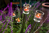 Recycled closet rods as candle holders night lighting in bed of Salvia in Matthew Levesque California garden