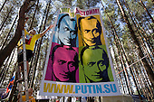 """Pro-Putin Nashi youths hang a poster of Russian Prime Minister Vladimir Putin at a summer camp on Lake Seliger in Russia. The headline reads: """"Together we will stand our ground!"""" The domain name .su refers to """"Soviet Union"""". Putin has called the collapse of the Soviet Union the greatest geo-political disaster of the 21st century. .This yearly camp, organised by the nationalistic group, trains youth in political activism."""