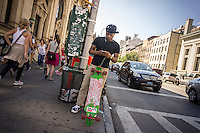 A skateboarder uses his smartphone to text in the New York neighborhood of Greenwich Village on Friday, July 26, 2013. ( © Richard B. Levine)