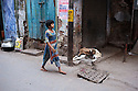A little girl is walking past a goat in the narrow streets of Old Delhi. New Delhi, India