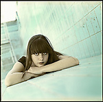 A young woman lying in an empty swimming pool