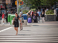 """A pedestrian using her smartphone crosses West 96th Street at Broadway in New York on Monday, August 4, 2014. As part of Mayor Bill de Blasio's """"Vision Zero"""" initiative the speed limit of 30 mph has been reduced to 25 mph. Broadway from West 59th Street to West 220 Street has been posted as a """"Slow Zone"""". with the other """"Slow Zone"""" starting today atSouthern Blvd. in the Bronx. Two dozen zones will be instituted in the five boroughs over the course of several months. 22 pedestrians have been killed since 2008 in the Broadway """"Slow Zone"""" and speeding is the top cause of traffic injuries and fatalities.   (© Richard B. Levine)"""