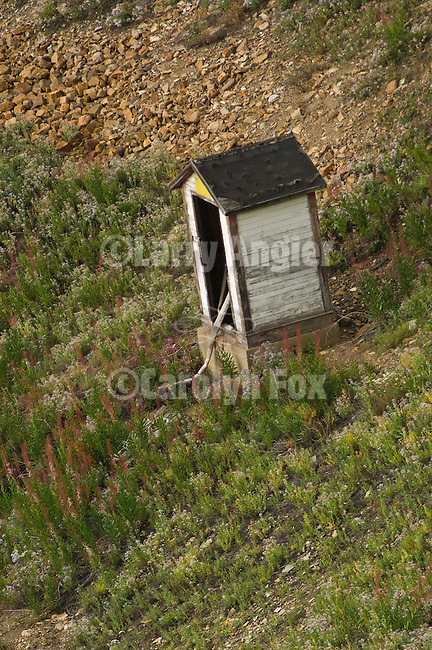 White wooden outhouse on a hillside at an old Colorado mining camp