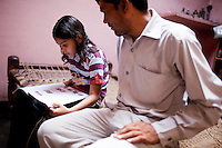 Jagroshan Sharma (aged 36, in grey) and his family in their home in Ghaziabad, Uttar Pradesh, India. Jagroshan had chosen to do a non-scalpel vasectomy (NSV) for many reasons. He wanted to be an equal partner in the relationship, knew that NSV was less complicated and will not put his wife through numerous problems, and wants his two children to do well in life and study in English medium schools despite his modest earnings. He now works part time as a link worker under the tutelage of Dr Meenal Mehta (unseen) who works with USAID on the NSV project in Uttar Pradesh, India. Jagroshan has been the star link worker, doing about 5 cases of NSV cases per month since he started. Photo by Suzanne Lee / Panos London