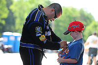 May 6, 2012; Commerce, GA, USA: NHRA top fuel dragster driver Brandon Bernstein (left) signs an autograph for a young fan during the Southern Nationals at Atlanta Dragway. Mandatory Credit: Mark J. Rebilas-
