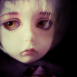 portrtrait of a sad doll with blonde hair and orange eyes