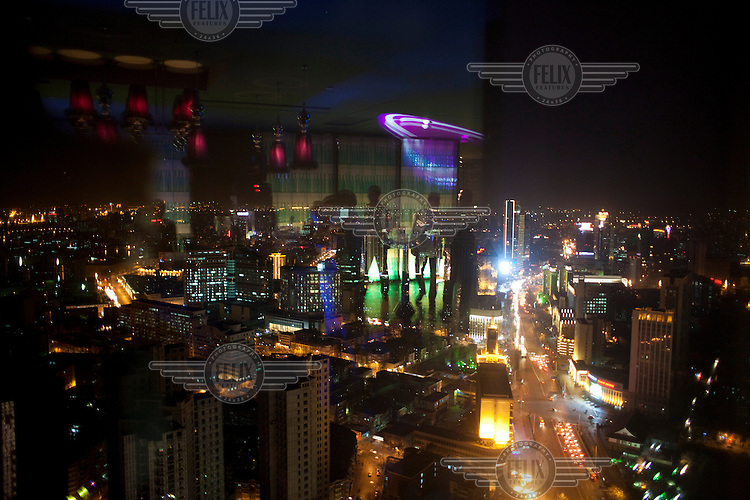 Patrons are reflected in a window of an exclusive hotel bar overlooking Tianjin.