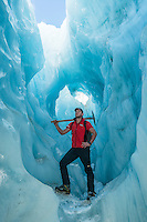 Glacier guide in amazing blue ice tunnel, cave on Franz Josef Glacier, Westland National Park, West Coast, World Heritage Area, South Westland, New Zealand