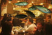 Fish swim in a tank in the window of a restaurant in the Kabukicho area of Shinjuku, whilst business men, known as 'salarymen', dine, smoke and drink inside. Tokyo, Japan.