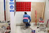 Tiling student in his work area, Able Skills, Dartford, Kent.