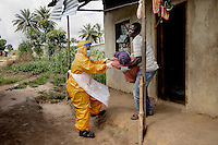 55 yearold Jariath Sesay, who is severely ill with ebola-like symptoms is helped by a man in PPE (personal protection equipment) from her home in Kissy Town to a treatment facility. Her son, who has been nursing her, is also helping her but has no protective clothing.