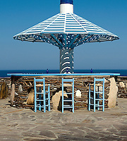 A trio of pale blue bar stools is lined up against a bar made of rough hewn stone beneath a 60s style wooden canopy overlooking the sea