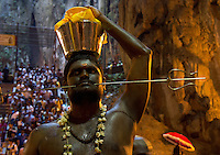 man with  Shivas fork-shaped spear thrilled through his cheeks while Thaipusam ceremonies inside Batu Caves, Kuala Lumpur, Malaysia, 2012. Thaipusam ceremonies, celebrated by tamile Hindu community in Malaysia, take place  in Sanctuary of Batu Caves at the border of Kuala Lumpur, each year around end of January or beginning of February, according to Hindu moon calendar. The event is paying hommage to Lord Murugan, a spirit or god created by Shiva to lead the army of gods against the army of evil demons, finally defeating the evil spirits. There are many ways to present offerings or sacrifices for this major religious event. Devotees mortify their bodies by carrying heavy kavaris with spears fixed in their skin or fruits, flowers and little post with holy milk fixed with hooks in their skin, ascending the stairways to the sanctuary in trance, `followed by assistant  taking care and musicians playing loud and fast rhythmic trance music.  Many families shave their head in a ritual before ascending the stairways, as part of rituals to obtain salvation for their ancestors.